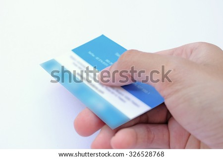 Business card on hand while handling it to others with bright background