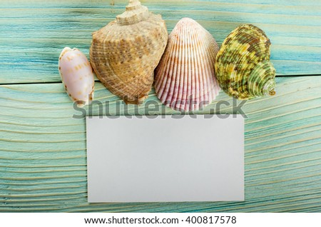 Business card, summer sea vacation mockup background. Notebook blank page with Travel items on blue green wooden table. Sea shells, pebbles, top view. - stock photo