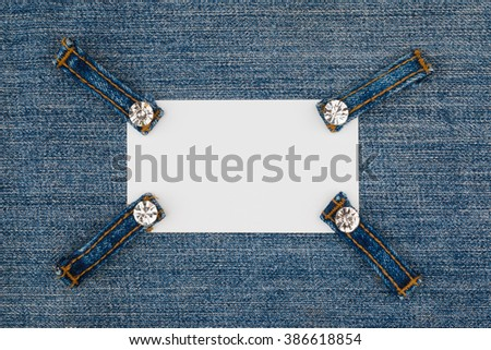 Business card with four straps jeans with rhinestones, lies on the  denim, with space for your text - stock photo