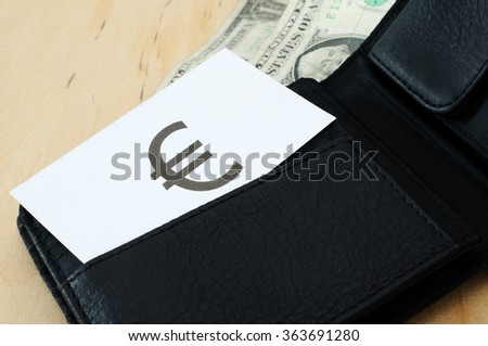 Business card with the sign EURO in wallet with dollars   - stock photo