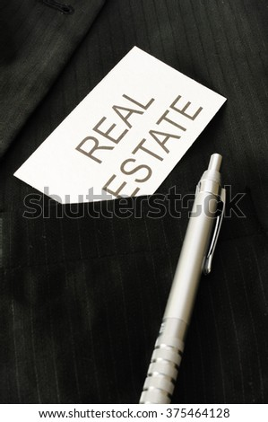 Business card with the sign REAL ESTATE  - stock photo
