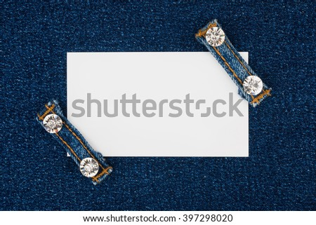 Business card with two straps jeans with rhinestones, lies on the  denim, with space for your text - stock photo