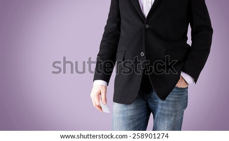 business casual man with a relaxed stance holding a business card with a lavender backdrop (shallow depth of field) - stock photo