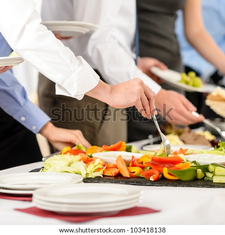 Business catering people take buffet food during company event - stock photo