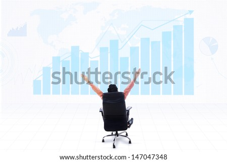 Business CEO sitting on a chair with his arms raised looking at profitable bar chart on world map - stock photo