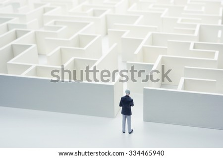 Business challenge. A businessman navigating through a maze. Rear view