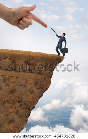 business challenge concept businessman pushed to the edge of a cliff - stock photo