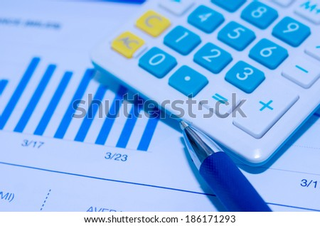 Business chart and Calculator is placed on the table.