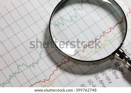 Business chart and magnifying glass, concept of analyzing. - stock photo