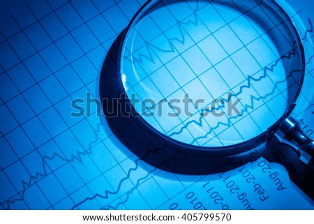 Business chart and magnifying glass, concept of analyzing.