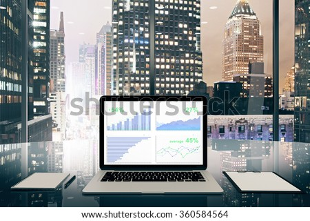 Business chart on laptop screen on glassy table in the office with night city view - stock photo