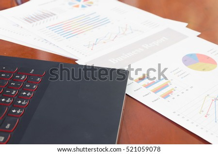 Business charts and laptop on wood desk