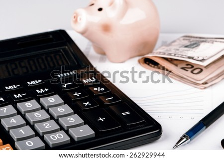 Business Charts with calculator, dollars money, piggy box / money box and pen on white background