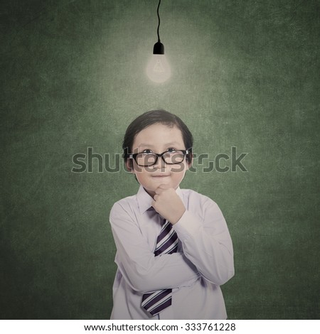 Business child is thinking under lit bulb in class - stock photo
