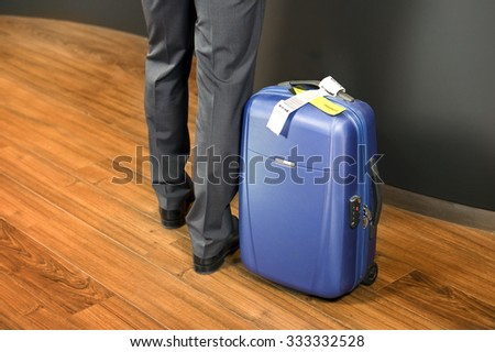 Business class passenger, with a carry on suitcase with priority luggage tags standing at an airport check-in counter - stock photo