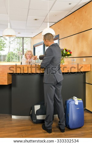 Business class passenger, with carry on luggage and priority airport labels checking in at a hotel, handing over his passport to the senior receptionist behind the counter - stock photo