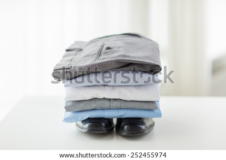 business, clothes, housekeeping and objects concept - close up of ironed and folded shirts, trousers and formal shoes on table at home - stock photo