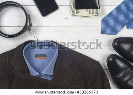 business clothes on a wooden background. set of men's clothing, shoes and accessories on wooden background.  Top view. Copy space for text. - stock photo