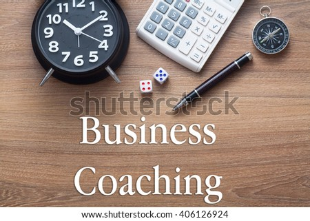 Business Coaching written on wooden table with clock,dice,calculator pen and compass - stock photo