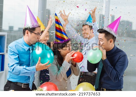 Business colleagues blowing up balloons at the office party