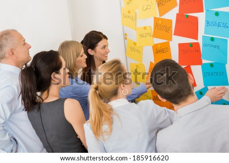 Business colleagues brainstorming multicolored labels stuck on whiteboard in meeting - stock photo
