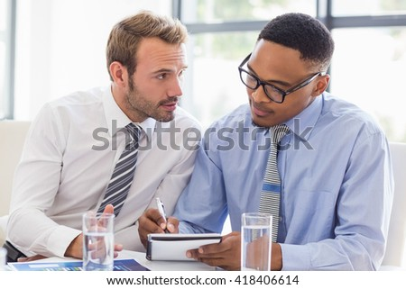 Business colleagues discussing a report in office - stock photo