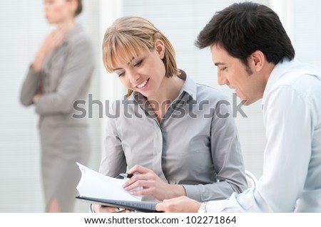 Business colleagues discussing on paperwork in a modern office - stock photo