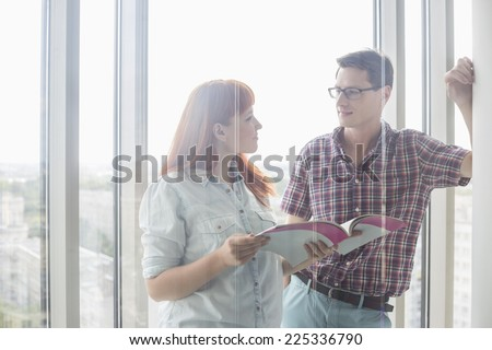 Business colleagues discussing over file in creative office - stock photo