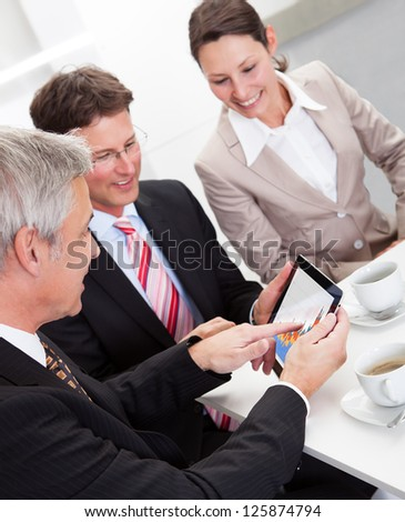 Business colleagues enjoying a coffee break smiling at something on the screen of a tablet held by one of the men - stock photo