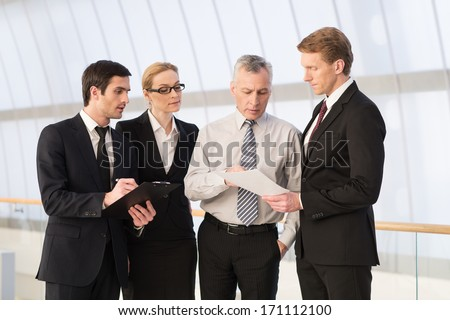 Business colleagues. Four people in formalwear discussing something while standing close to each other - stock photo