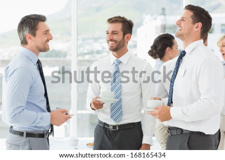 Business colleagues in discussion with tea cups during break at a bright office