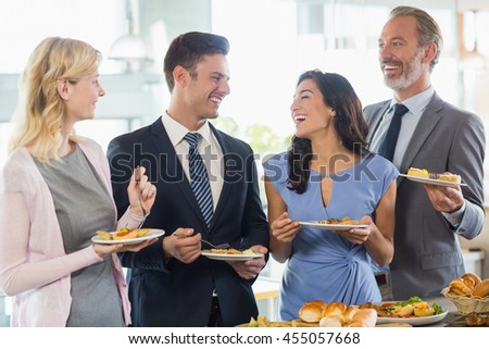 Business colleagues interacting while serving themselves at buffet lunch in a restaurant - stock photo
