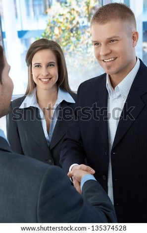 Business colleagues introducing with handshake, standing in office, smiling. - stock photo