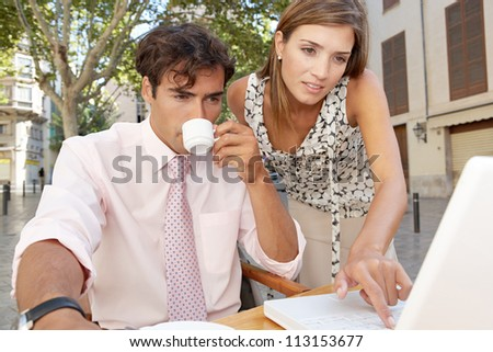 Business colleagues looking at a laptop screen while having a meeting in a coffee shop terrace, outdoors.