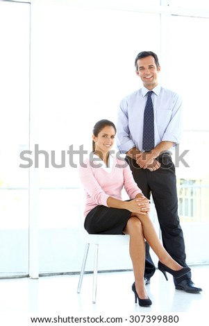 Business colleagues. Portrait of a businessman and a businesswoman. She sits on a chair, he is standing next to her. She wears a pink jersey, he has a blue shirt and a tie.  - stock photo