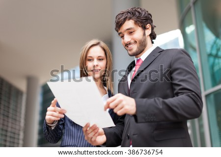 Business colleagues reading a document outdoor