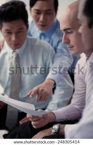 Business colleagues reading document, selective focus - stock photo