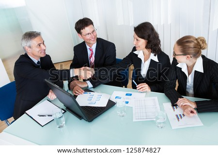 Business colleagues seated around a table in a meeting congratulating one another by shaking hands