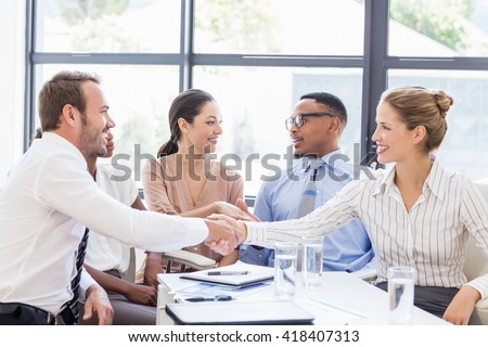 Business colleagues shaking hands during a meeting in office