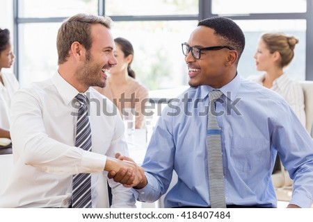 Business colleagues shaking hands during a meeting in office - stock photo