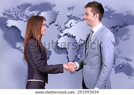 Business colleagues shaking hands on world map background - stock photo