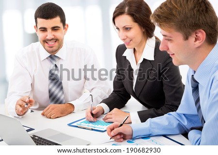 Business colleagues sitting around table and working together - stock photo