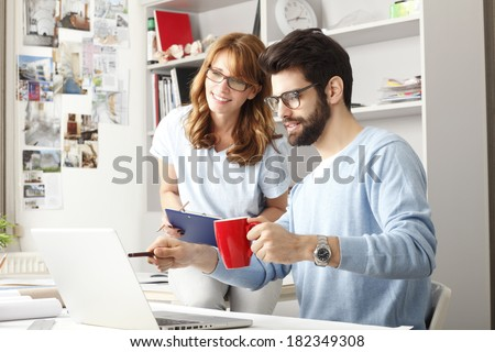 Business colleagues sitting at desk and working on small architect studio.  - stock photo