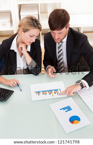 Business colleagues sitting together at a table in an office discussing and analyzing a bar graph - stock photo