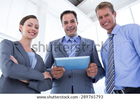 Business colleagues smiling at camera and holding tablet in the office