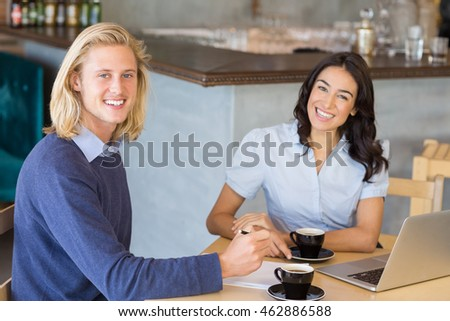 Business colleagues smiling while having a cup of tea in restaurant