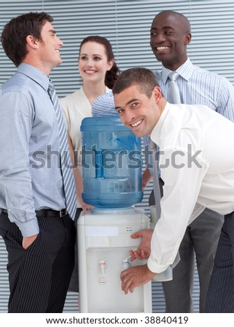 Business colleagues talking around water cooler in workplace
