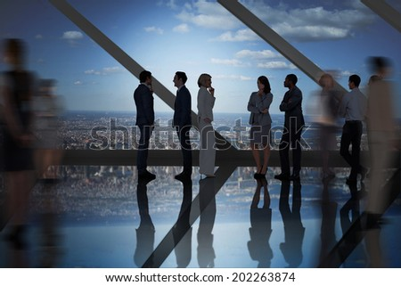 Business colleagues talking in large room overlooking city - stock photo