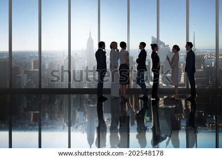 Business colleagues talking in large room overlooking city