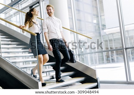 Business colleagues talking on stairs and flirting while smiling - stock photo